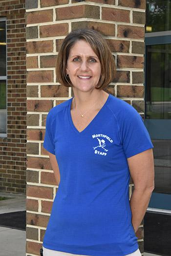 Principal Cassandra Lopez in front of school building